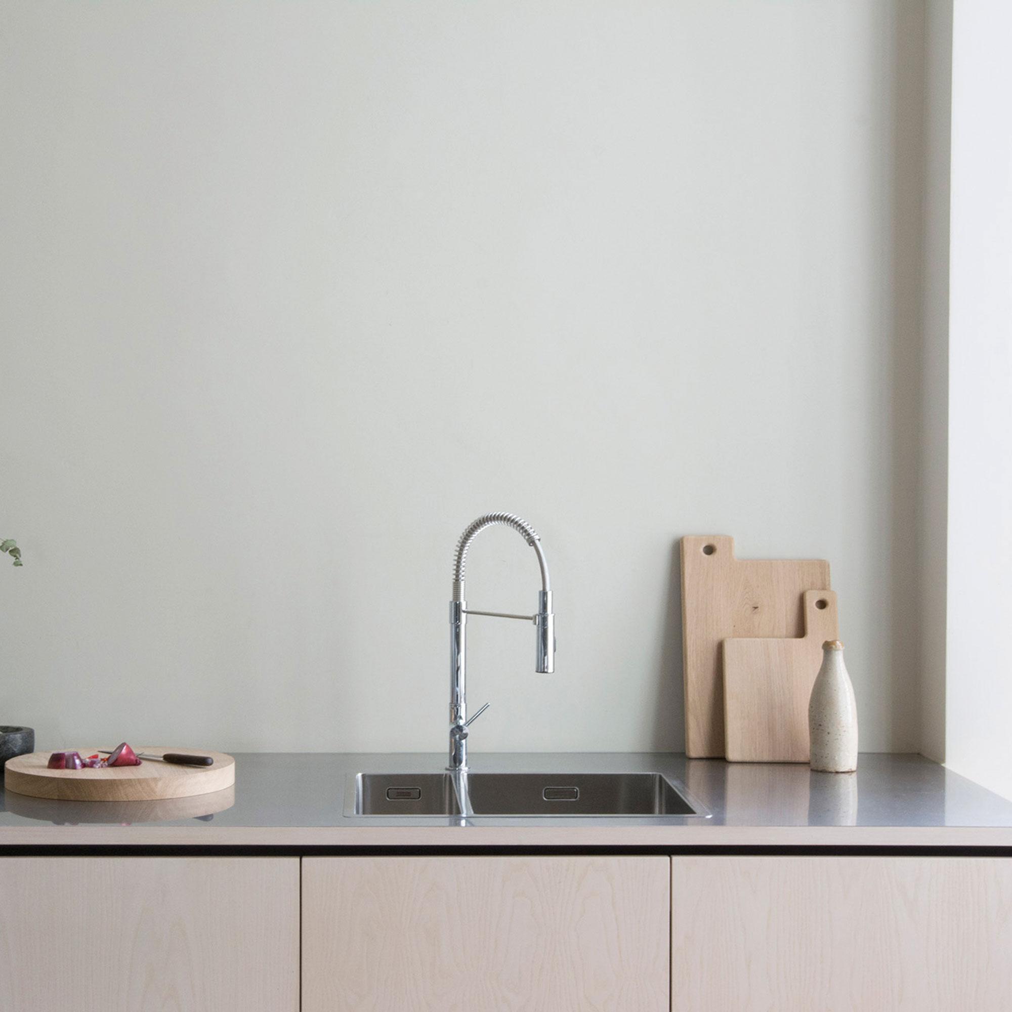 reduzierte Küche mit gekalkten Eschefronten und Arbeitsplatte aus Edelstahl