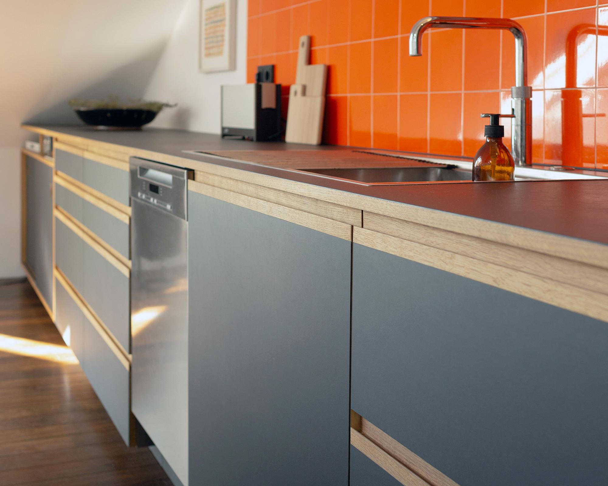 Maisonette Küche mit orangenen Fliesen, anthrazit farbendem Linoleum und Griffleisten aus Eiche